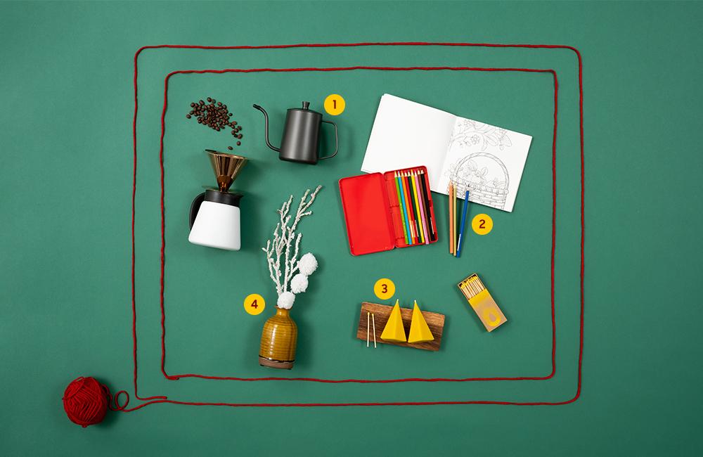 더 프레임 모양으로 만들어진 털실 안에 커피 드리퍼 세트, 컬러링 북과 색연필, 향초, 화병과 꽃이 있는 모습