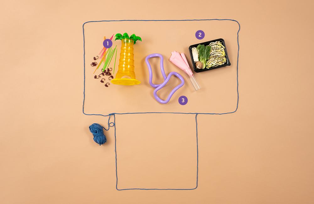 더 세로 모양으로 만들어진 털실 틀 안에 보드게임, 밀키트, 운동 소도구가 놓여있는 모습