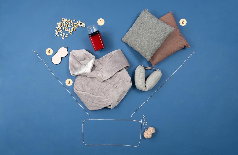 더 프리미어 모양으로 만들어진 털실 틀 안에 팝콘 메이커, 쿠션&목베개, 입는 담요, 안대가 놓여있는 모습