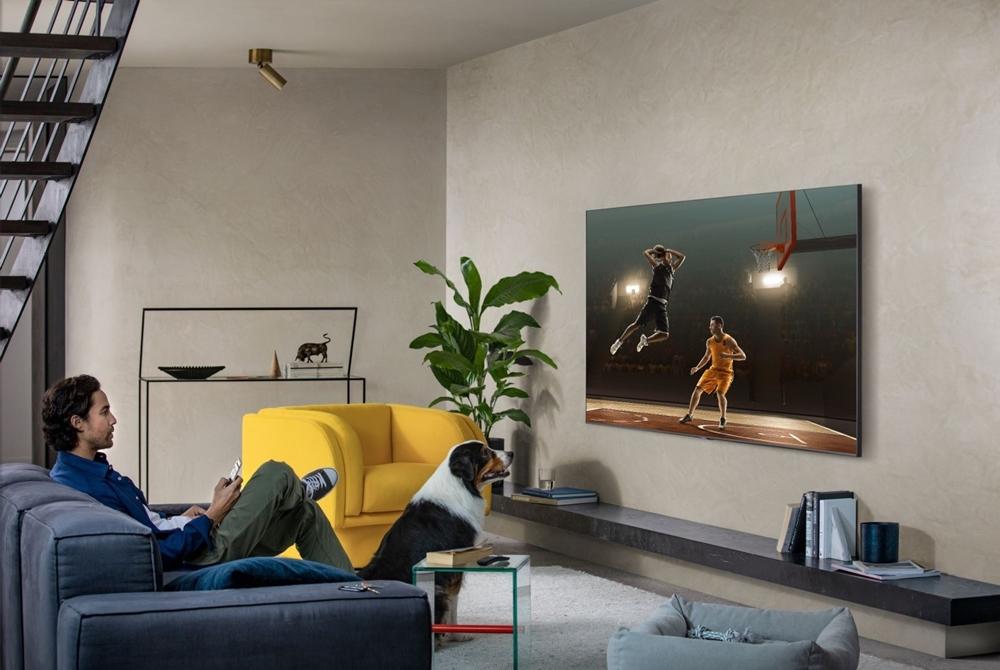 QLED TV로 거실에서 농구 경기를 보는 남자
