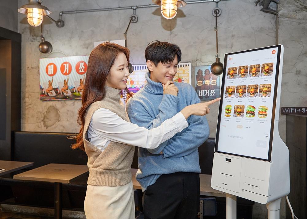 삼성전자 모델이 서울 성동구에 위치한 햄버거 전문점 '버거쇼'에 설치된 신제품 '삼성 키오스크'를 소개하고 있다.