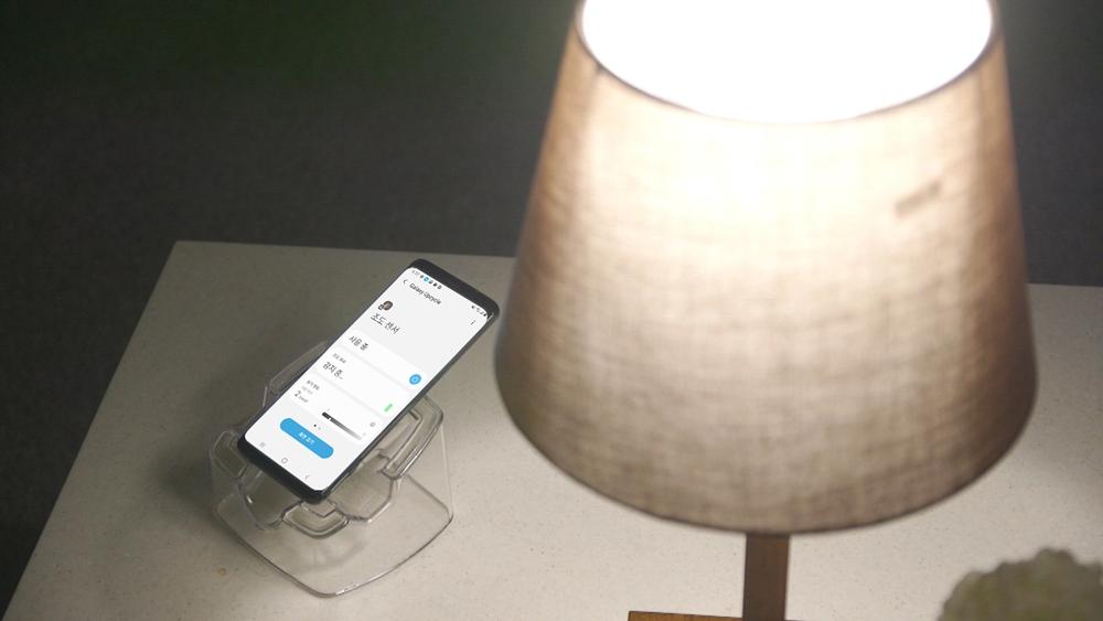 삼성전자 갤럭시 S9으로 '갤럭시 업사이클링 앳 홈'을 사용하고 있는 이미지. 갤럭시 스마트폰의 조도 센서를 사용해 사전에 설정한 조도 기준 이하로 주변 환경이 어두워지면 연동해 놓은 조명이 켜진다.
