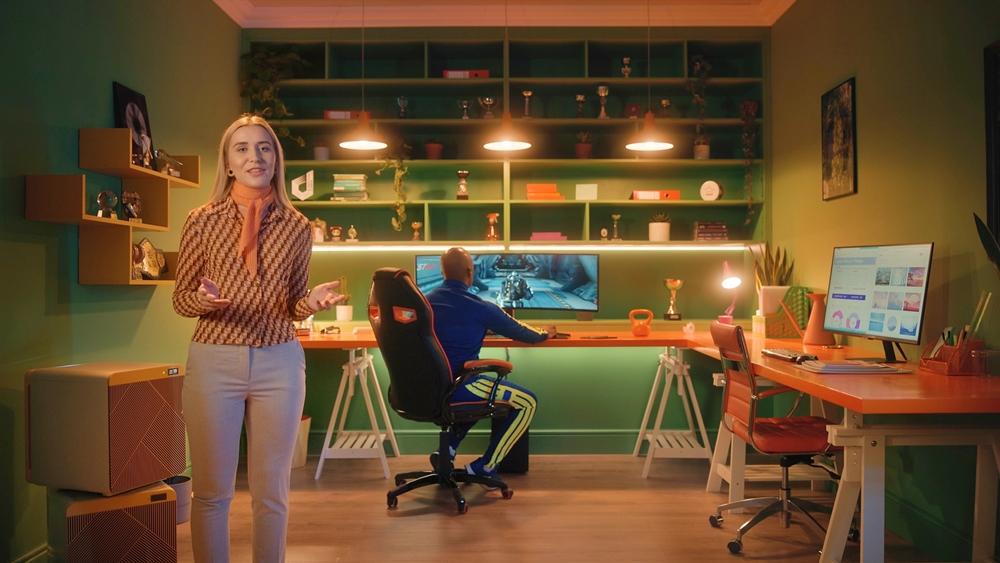 게임하는 남자가 보이고 여자는 삼성전자 제품들을 소개하고 있다